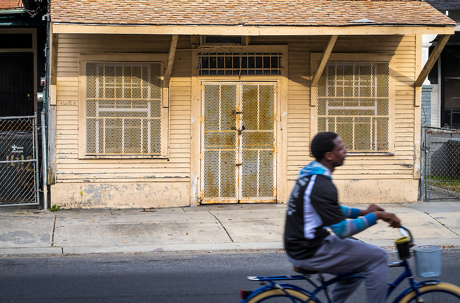 NEW ORLEANS - CIRCA FEBRUARY 2014: Young man riding a bicycle in the streets of McDonough, a popular community within the city of New Orleans in Louisiana.