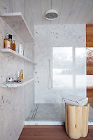 The walls of this contemporary shower room are lined with Carrara marble and the wooden side table is by Paola Navone