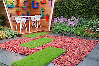 Heucheras and lawn grass in pretty pattern next to deck, patio furniture, herb planter boxes mounted on wall, Silene in flower