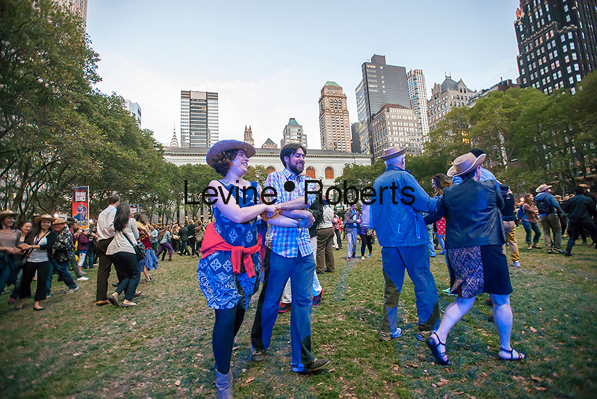 Hundreds of New Yorkers and visitors dance up a storm in Bryant Park in New York on Wednesday, September 25, 2013 during the third and last square dancing session of the year in the park. As incongruous as it sounds square dancing's popularity in New York ebbs and flows with it reaching its peak after World War II where thousands would participate in large dances held in Central Park. (© Richard B. Levine)