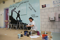 Aliya Ali Abdelqader, an eleven year old   middle school student, cleans up after joining classmates to paint a mural against hate at a middle school in the borough of Brooklyn in New York on Sunday, March 25, 2012.  The mural was part of the Anti-Defamation League No Place for Hate program.  (© Frances M. Roberts)