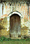 Old Wooden Door - Old arched wooden door in the crumbling weathered wall of an abandoned French colonial style villa, Bac Ha, NW Viet Nam