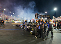 Jun 19, 2015; Bristol, TN, USA; Crew members push NHRA top fuel driver Larry Dixon forward to the burnout box during qualifying for the Thunder Valley Nationals at Bristol Dragway. Mandatory Credit: Mark J. Rebilas-