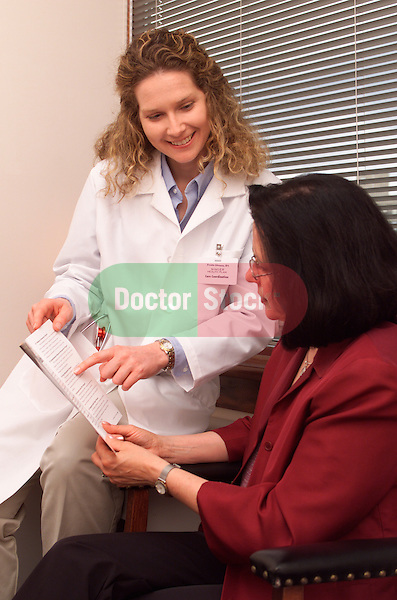 female doctor showing female patient health issue literature in examination room