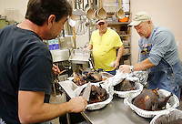 NWA Democrat-Gazette/DAVID GOTTSCHALK  Doug Foley (from left) and Mark Foster begin to prepare the turkeys Wednesday, November 25, 2015, smoked by Billy Tester, of the White Star Tavern in Fayetteville, at the American Legion Post 27 in Fayetteville. The tavern donated the cooking of the turkeys for the traditional style meal. The meal, normally served today, was served Wednesday so that those in need would have an opportunity for an additional meal.