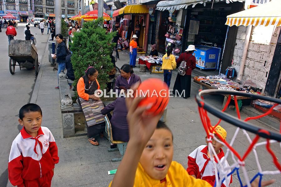 Crinças jogando basquete em rua comercial. Lhasa. Tibet. China. 2007. Foto de Caio Vilela.