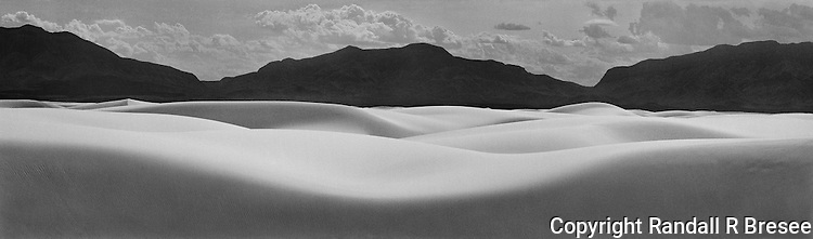 &quot;New Mexico Waves&quot; White Sands National Monument, New Mexico<br /> This scene at White Sands National Monument provided an opportunity to contrast dark mountains with the bright sand. I composed a photo to suggest that the natural formations were like waves flowing across the landscape. Of course, constantly changing sand dunes are exactly that. Proper exposure and development of the negative were critical to this black and white photo since the dark mountains and bright sand both required good detail.