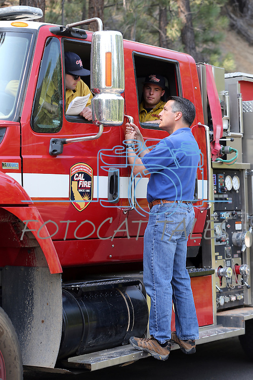 Nevada Gov. Brian Sandoval, left, and U.S. Secretary of the Interior Sally Jewell, right, talk with Cal Fire Engineer Josh Clelland, left, and Firefighter Tyler Lopez in Markleeville, Ca. on Wednesday, June 24, 2015. The lightning-caused Washington fire has grown to nearly 17,000 acres since Friday.  <br /> Photo by Cathleen Allison