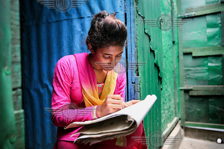Jhuma Akter studying in the evening inside the family home.