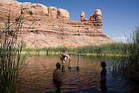 Guide John Humphries dives from a makeshift platform as cyclists Kip and Aaron (11) Sharpe take advantage of the local swimming hole -- a small reservoir among the sandstone walls -- at Bluff, Utah, June 30, 2010. The Red Rock Canyons Tour, organized by Lizard Head Cycling Tours, wound through 400 miles of the desert southwest. The route traveled through canyons and national monuments in Colorado, Utah and Arizona, ending at Lake Powell. (Kevin Moloney for the New York Times)