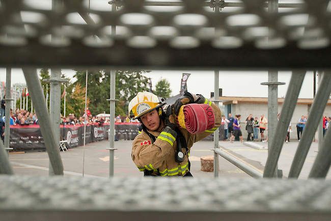 Vancouver, Canada, Aug 6th 2009.  World Police and Fire Games, Ultimate Firefighter Competition. Competitor Scott Linton of the Calgary Fire Department, Alberta, Canada, makes his way up the stairs, while carrying a high-rise pack (100 feet of 1½-inch hose).  A scaffold with stairs was set up to represent a building for the Weight and Strength Stage of the competition.  Photo by Gus Curtis
