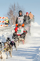 Andrew Nolan and team run past spectators and down the Cordova Street hill with an Iditarider in the basket and a handler during the Anchorage, Alaska ceremonial start on Saturday March 4th during the 2017 Iditarod race. Photo ©2017 by Daniel Lent/SchultzPhoto.com