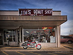 Motorcyle (Harley Davidson) parked outside of Jim's Donut shop.