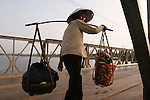CAMBODIA  -  APRIL 3, 2005:  A elderly woman carrying produce crosses the Kampot River on a bridge on April, 3, 2005 in Kampot, Cambodia. (PHOTOGRAPH BY MICHAEL NAGLE).