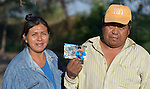 A Wichi indigenous couple, Graciela Sarabia and Jose Luis Fernandez, pose with a photo of them taken seven years earlier at their home in Lote 75, an indigenous neighborhood of Embarcacion, Argentina. The Wichi in this area, largely traditional hunters and gatherers, have struggled for decades to recover land that has been systematically stolen from them by cattleraisers and large agricultural plantations.
