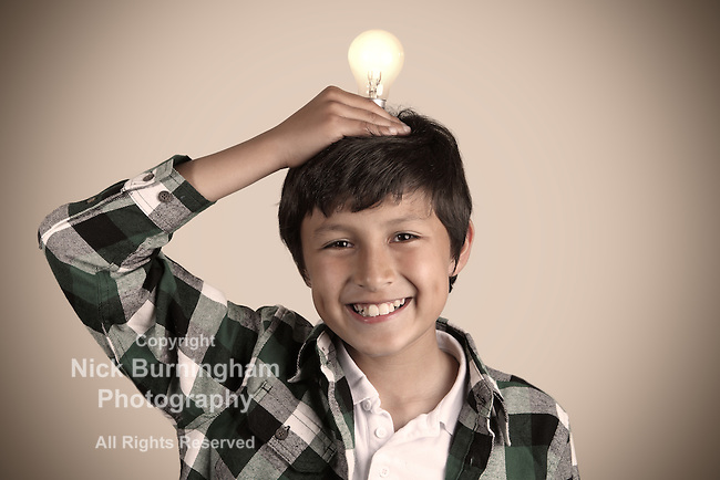 Young boy holding light bulb on his head