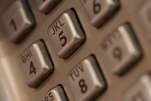 Close up macro shot of a public telephone key pad, some filter added for effect, communications background