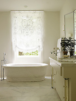 The weight of a white marble bath is offset by the diaphanous lace curtain across the window behind it