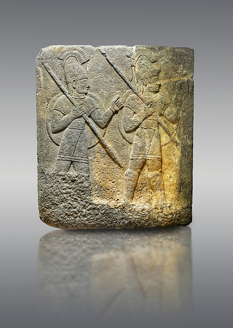 Hittite relief sculpted orthostat stone panel of Herald's Wall. Limestone, Karkamıs, (Kargamıs), Carchemish (Karkemish), 900-700 B.C. Military parade. Anatolian Civilisations Museum, Ankara, Turkey.<br /> <br /> Three helmeted soldiers in short skirts carry the shield on their backs and the spears in their hands. The bottom right part of the relief was left untreated since the pedestal stood in front of it.