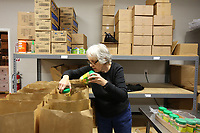 Kathy Kingsbury, a volunteer at FEED the 479 food pantry at the Compassion Center, packs United States Department of Agriculture food bags for distribution at the center in Springdale. FEED the 479 is changing to a drive through method to pick up food items. The food can be picked up on Monday and Thursday from 9:30 a.m. to 11:30 a.m. and Tuesday and Wednesday from 5:00 p.m. to 7:00 p.m.. Check out nwaonline.com/200319Daily/ and nwadg.com/photos for a photo gallery.<br /> (NWA Democrat-Gazette/David Gottschalk)