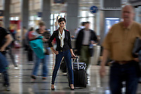 Businesswoman with suitcase in the terminal at the Austin–Bergstrom International Airport (ABIA), intentional motion blur.