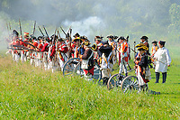 British artillery unit, in blue coats with red facings, and redcoats prepare to fire during a Revolutionary War re-enactment at Fort Ticonderoga, New York, USA.