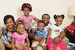 Parents with children 18 months-7 years old posing for family portrait, sitting on couch at home