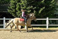 Mädchen beim Reitunterricht auf Ponyhof, Mädchen reitet im Galopp auf ihrem Reitpony auf dem Reitplatz, Reiten, Reiterhof, Gestüt