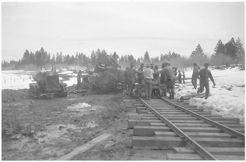 A view along the track of New Mexico Lumber Co. #4 (ex D&amp;RGW #227) overturned on the Long Draw Branch of the logging railroad with the repair crew having installed several long ties.  The Caterpillar 60 tractor used to do the heavy moving is alongside.<br /> New Mexico Lumber Co.  San Juan National Forest - Long Draw Branch, CO  Taken by Long, Morris - 3/1928