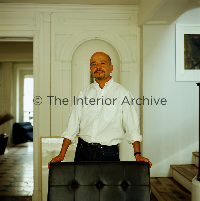 Portrait of interior designer Frederic Mechiche standing in his library