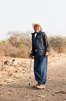 Lareano Vazquez, 82 years old, is a representativeof the Ejido (communal land) from which Edgar has permission to harvest. Edgar Angeles harvesting a wild Karwinskii maguey also known as Largo, Serial or Tovasiche to be later cooked and distilled for mezcal. Mezcal Real Minero, Ocotlan de Morelos, Oaxaca, Oaxaca, Mexico