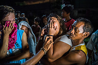 "MANILA, PHILIPPINES - OCTOBER 02: Elise Rufino, held by a family member, grieves for her husband, Joselito Rufino Jumaquio, 52, who was killed by unidentified masked police, in what the police called an alleged ""buy bust"" operation on October 02, 2016 in Manila, Philippines. According to neighbors, at 9pm, at least 15 unidentified plain clothed police wearing masks, descended over the close railway side community quickly and silently. Roel, 13, Joselito's nephew, was playing a videogame with his uncle in small stall when the men grabbed his uncle and handcuffed him. They dragged the powerless pedicab driver towards the alleyway behind the stall and shouted at residents still gathered to go back into their homes and to turn their lights off. The residents then only reported what they heard. A woman's voice shouted ""He's fighting it out,"" or Nanlaban, a term used in many police reports to justify the use of lethal force. Two shots rang out - then 4 more. After the group left, neighbors discovered Joselito's bloodied body, a gun placed next to his handcuffed hands and a white plastic bag with methamphetamine. According to police, this was a legitimate buy bust operation where the handcuffed target drew a .38 calibre handgun and then, ""Sensing that his life was in serious danger, the lawman was constrained to fire back in order to protect his life against the armed aggressor."" After the men left they found Joselito handcuffed and found his body with a gun was placed next to him and a white plastic bag full of narcotics placed on his dead body. Elisa, Joselito's wife, arrived at the scene and started to confront police when she found out the news. Family and friends tried to restrain her but she continued. An angry crowd of residents gathered and started shouting at the police.""We curse you,"" they yelled, citing the countless times those arrested have been killed on the grounds that they were fighting back. ""You have no pity. We are poor, and we are alo"