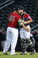 Hickory Crawdads relief pitcher Joe Filomeno (31) gets a hug from catcher Chuck Moorman (29) after closing out the game against the Charleston RiverDogs at L.P. Frans Stadium on August 25, 2015 in Hickory, North Carolina.  The Crawdads defeated the RiverDogs 7-4.  (Brian Westerholt/Four Seam Images)
