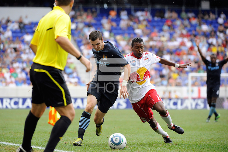 Adam Johnson (11) of Manchester City F. C. and Danleigh Borman (11) of the New York Red Bulls. The New York Red Bulls defeated Manchester City F. C.2-1 during a Barclays New York Challenge match at Red Bull Arena in Harrison, NJ, on July 25, 2010.