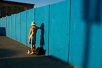 A woman leans against a blue wall as she makes a cell phone call. Street photography in Conney Island, Brooklyn,  NY August 4, 2007
