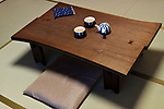 Japanese tea table, Chabudai with a teapot and two cups, Zabuton sitting cushion on tatami mats of a traditional Japanese room in a Ryokan inn in Kyoto, Japan