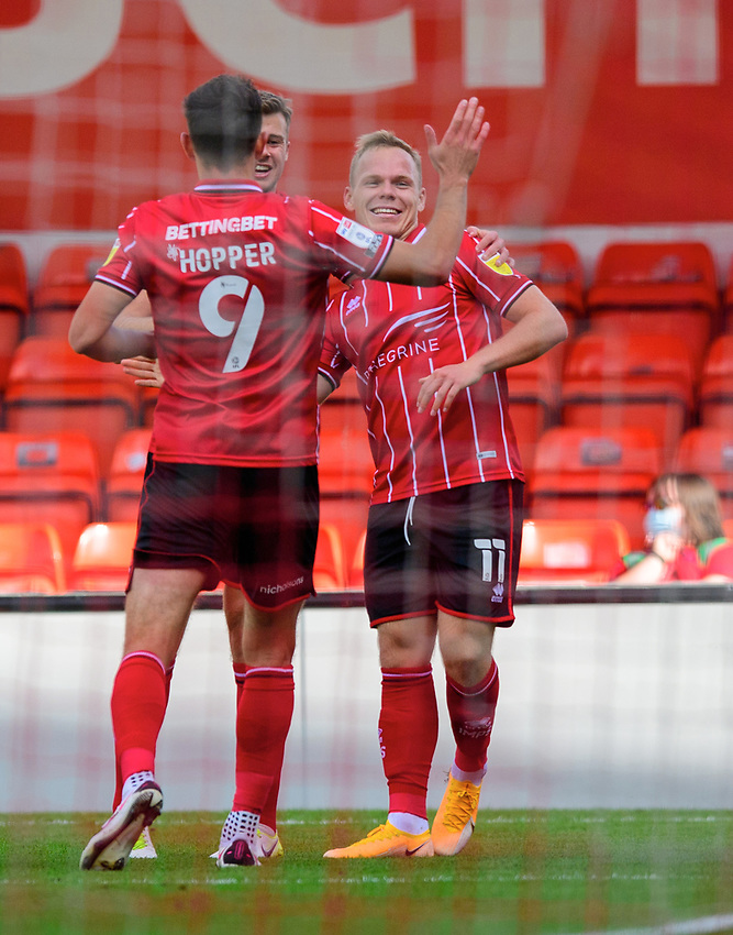 Lincoln City's Anthony Scully, right, celebrates scoring the opening goal with team-mates Tom Hopper, left, and James Jones<br /> <br /> Photographer Chris Vaughan/CameraSport<br /> <br /> The EFL Sky Bet League One - Saturday 12th September 2020 - Lincoln City v Oxford United - LNER Stadium - Lincoln<br /> <br /> World Copyright © 2020 CameraSport. All rights reserved. 43 Linden Ave. Countesthorpe. Leicester. England. LE8 5PG - Tel: +44 (0) 116 277 4147 - admin@camerasport.com - www.camerasport.com - Lincoln City v Oxford United