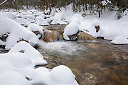 Pine Brook along the East Pond Trail during the winter months in Lincoln, New Hampshire USA, which is part of the White Mountain National Forest