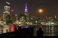 HOBOKEN, NJ - APRIL 11: A man looks at The Empire State Building lit purple and gray in honor of the 100th anniversary of the New York state police while moon rise over middle Manhattan as it is seen from the shore on April 11, 2017 in Hoboken, New Jersey. Since April 11, 1917, the State Police have been committed to helping New Yorkers by providing them with friendly, professional service. Photo by VIEWpress/Eduardo MunozAlvarez