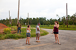 Mike Porter (left to right), his sister Amanda Porter and her father Paul, and neighbor Bebe Goolsby wait for the school bus to drop off Bebe and Amanda's children in Vaughn, a small community in Georgia that was devastated by a tornado in April.