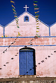 Natal, Brazil. Small whitewashed church with blue painted doors, bell and bunting flags. Rio Grande do Norte State.