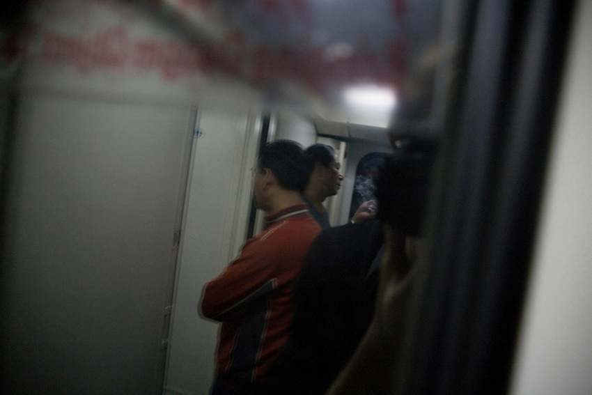 Passengers waiting and smoking in the corridor of he train from Guangzhou to Beijing, reflection on the window.. Feb 2010.
