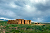 USA, Wyoming, Encampment, freshly stacked hay bales in an open meadow under a stormy sky, Big Creek Ranch