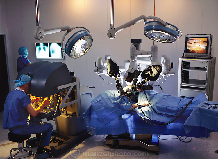 Robot surgery. Surgeon (lower left) performing minimally invasive surgery (MIS) on a patient's heart using da Vinci, a remotely-controlled robot surgeon (centre right). The surgeon views a three- dimensional image of the operation site in the black box at left. The robot arms are controlled using instruments under the box. An endoscopic view of the area from the robot is seen at upper right. Another surgeon is examining chest X-rays at upper left. The da Vinci system allows precise control of surgical tools through an incision just 1cm wide, with greater control than manual MIS procedures. Da Vinci was designed by Intuitive Surgical Incorporated, based in California, USA.