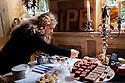 London, UK. 07.02.2015. Laura perfects her cakes with a paintbrush in preparation for 'Saturday Super Salon' at 40 Winks Hotel, Stepney. 40 Winks Hotel is a boutique hotel, owned and run by interior designer, David Carter, who hosts 'Saturday Super Salon'. This 'Saturday Super Salon' is the first in a series of interviews by journalist, Liz Hoggard, followed by discussion and refreshments. This Saturday, she interviews Kerstin Rodgers (aka MsMarmiteLover), food writer and Underground Supper Club originator. Photograph © Jane Hobson.