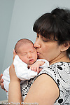 3 day old newborn baby boy asleep kissed by mother