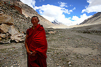 "Monk Lobsang Cheodeng  stands in front of Rongbuk Monastery near Everest base camp.China started building a controversial 67-mile ""paved highway fenced with undulating guardrails"" to Mount Qomolangma, known in the west as Mount Everest, to help facilitate next year's Olympic Games torch relay."