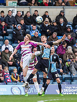 Harry Taylor of Barnet and Stephen McGinn of Wycombe Wanderers in the air during the Sky Bet League 2 match between Wycombe Wanderers and Barnet at Adams Park, High Wycombe, England on 16 April 2016. Photo by Andy Rowland.