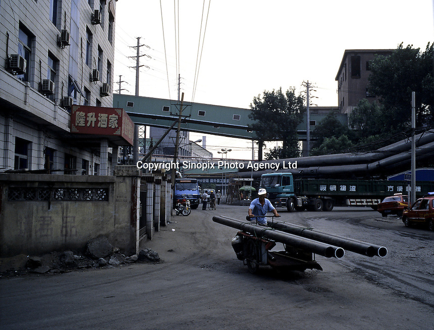 A man conveys steel tubes by a tricycle out of Anshan Iron & Steel Group in Liaoning. China's second-largest steelmaker Anshan Iron & Steel Group has merged with smaller rival Benxi Steel Group to create a company with capacity that will match the mainland's biggest steelmaker, Shanghai Baosteel Group..22 Aug 2005