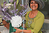 Mother of the bride at wedding ceremony with bouquet of flowers.